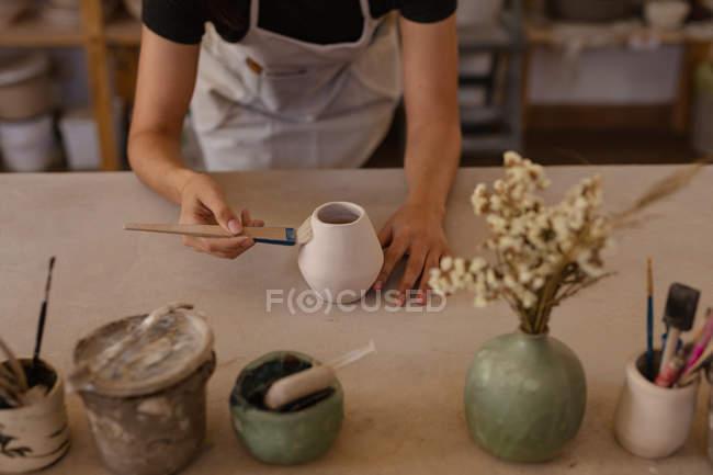 Erhöhte Ansicht einer Töpferin, die sich über einen Arbeitstisch lehnt und in einem Töpferatelier einen Topf glasiert, mit Töpfen und Werkzeug im Vordergrund — Stockfoto