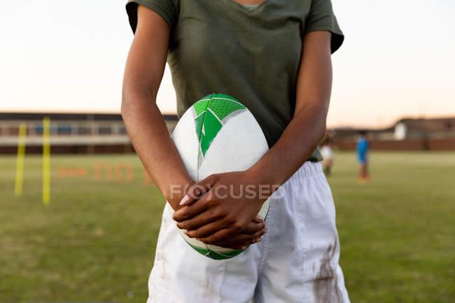 Передня частина жіночого регбі-гравця стоїть на спортивному полі з регбі м'ячем під час тренувань. — стокове фото
