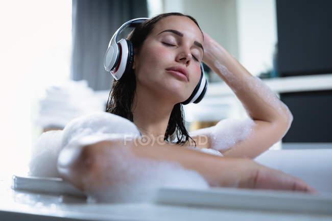 Вид спереди на молодую брюнетку, сидящую в пенной ванне в наушниках и слушающую музыку с закрытыми глазами — стоковое фото