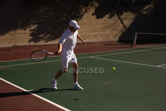 Vista lateral de um jovem caucasiano jogando tênis em um dia ensolarado, batendo uma bola com uma parede atrás dele — Fotografia de Stock