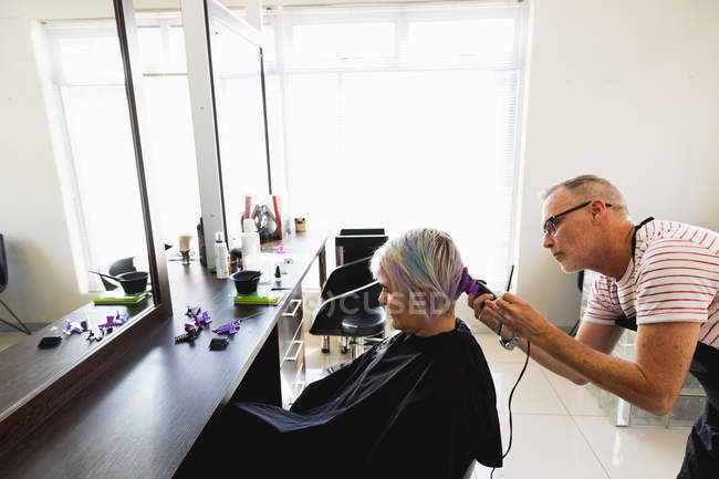 Side view of a middle aged Caucasian male hairdresser and a young Caucasian woman having her hair trimmed in a hair salon — стокове фото