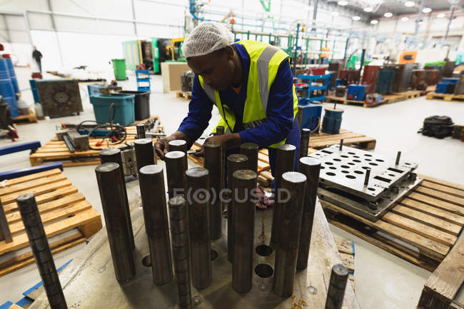 Front view close up of a young African American male factory worker preparing a machine part in a warehouse at a processing plant — Stock Photo