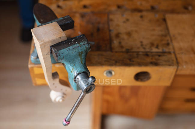 Close up of a vice with the scroll of a violin attached to a workbench in a workshop — Stock Photo