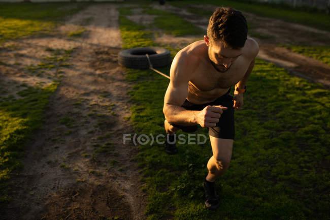 Vue de face d'un jeune homme caucasien torse nu tirant un pneu sur une corde autour de sa taille dans une salle de gym extérieure lors d'une séance d'entraînement bootcamp — Photo de stock