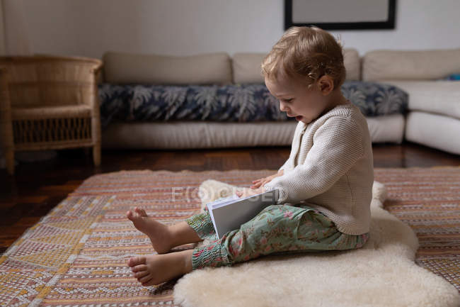 Side view of a Caucasian baby sitting on a floor and holding a notebook, barefoot — Stock Photo