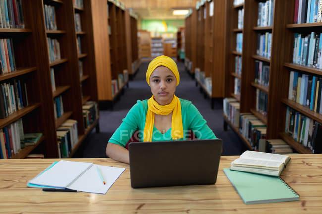 Ritratto di una giovane studentessa asiatica che indossa un hijab usando un computer portatile e studia in una biblioteca — Foto stock