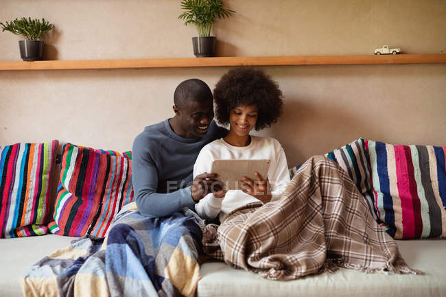 Front view close up of a young mixed race woman and a young African American man looking at a tablet computer and talking sitting together on a sofa at home. — Stock Photo