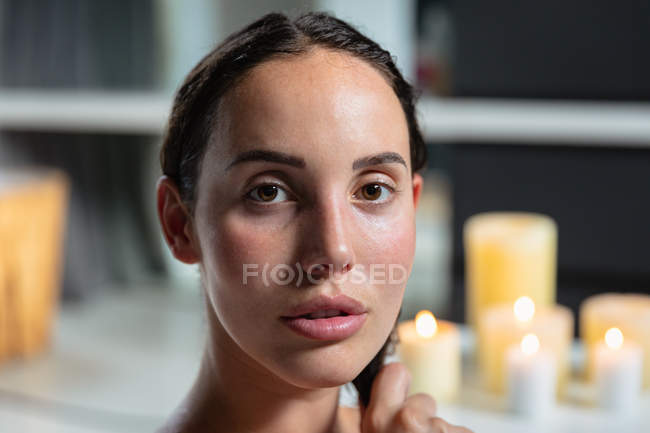 Portrait close up of a young Caucasian brunette woman sitting in a bath with lit candles on the side behind her, looking straight to camera — Stock Photo
