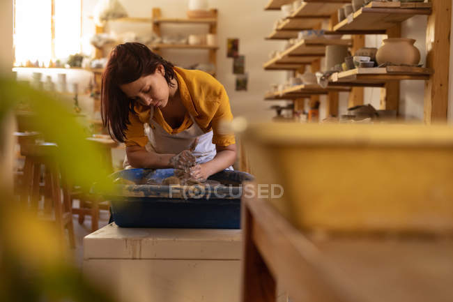 Front view of a young Caucasian female potter sitting and working with clay on a potters wheel in a pottery studio, with equipment in the foreground — Stock Photo