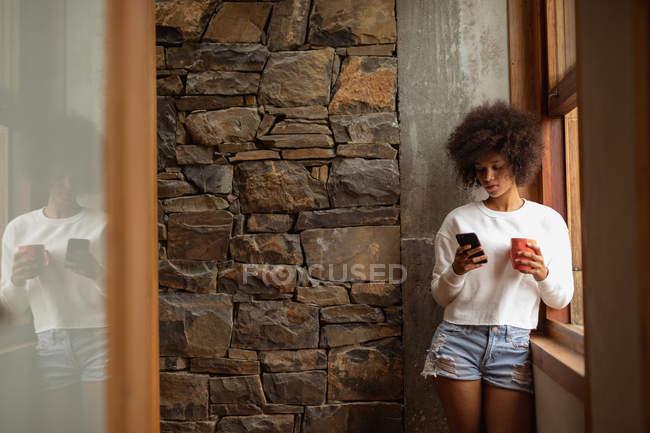 Вид спереди на молодую женщину смешанной расы, стоящую у окна, использующую смартфон и держащую чашку кофе — стоковое фото
