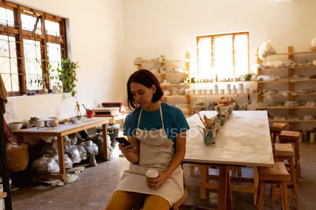 Вид спереду молодий Кавказький жіночий Поттер носіння фартух сидить на стільці за допомогою смартфона і проведення винос кави в гончарної студії — стокове фото
