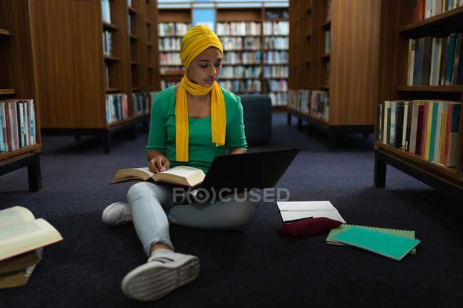 Vista frontale da vicino di una giovane studentessa asiatica che indossa un hijab con in mano un libro, usa un computer portatile e studia in una biblioteca — Foto stock