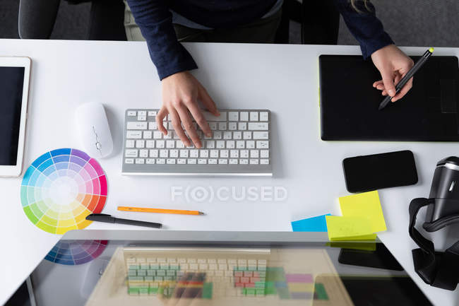 Overhead-Ansicht der Hände einer Frau, die im modernen Büro eines kreativen Unternehmens an einem Schreibtisch mit einer Computertastatur und einem Grafik-Tablet sitzt — Stockfoto