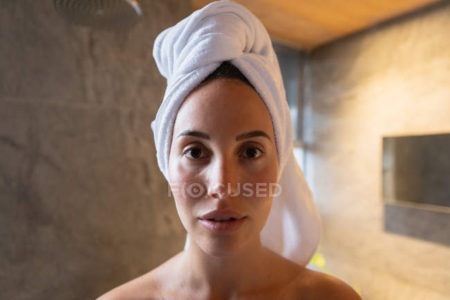 Portrait close up of a young Caucasian brunette woman with her hair wrapped in a towel, looking straight to camera in a modern bathroom — Stock Photo