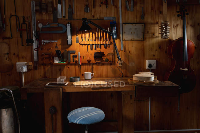Violin being made in a luthier workshop with tools hanging up on the wall in the background — Stock Photo
