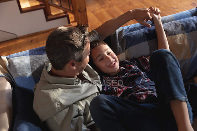 Side view of a middle aged Caucasian man sitting with his pre teen son on a couch and talking — Stockfoto