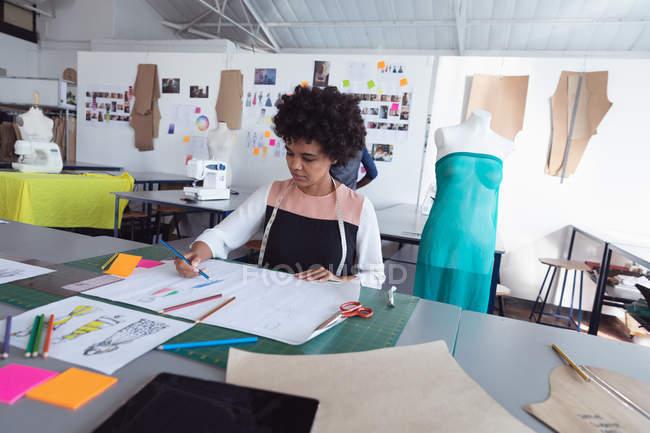 Vista frontal de una joven estudiante de moda de raza mixta que trabaja en un diseño en un estudio de la universidad de moda - foto de stock