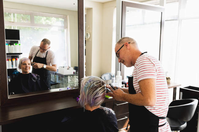 Side view of a middle aged Caucasian male hairdresser and a young Caucasian woman having her hair trimmed in a hair salon, reflected in a mirror — стокове фото
