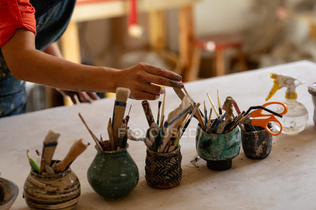 Close up of the hand of a female potter standing and selecting a tool from pots of tools on a work table in a pottery studio — Stock Photo