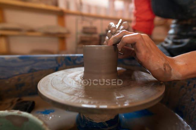 Seitenansicht Nahaufnahme der Hände weiblicher Töpferinnen, die auf einer Töpferscheibe in einem Töpferatelier feuchten Ton zu einer Topfform formen — Stockfoto