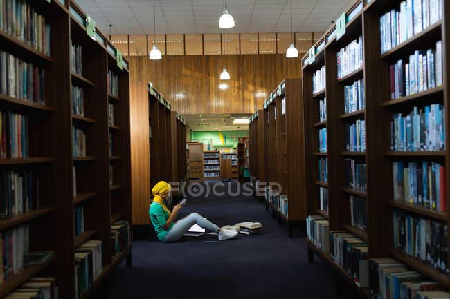 Вид сбоку на молодую студентку азиатского происхождения, которая носит хиджаб с помощью смартфона и учится в библиотеке — стоковое фото
