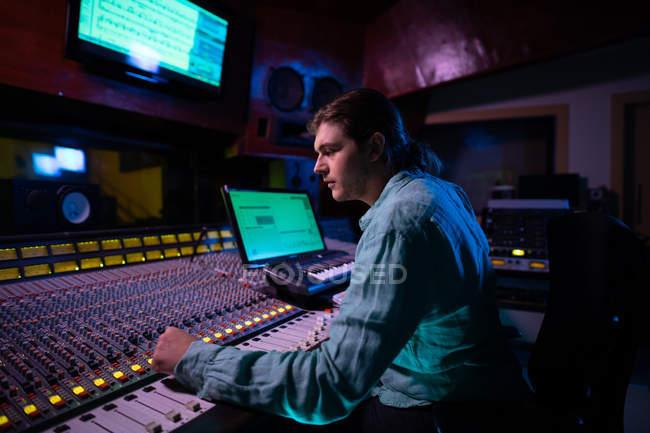 Вид сбоку на молодого кавказского звукоинженера, сидящего и работающего за микшерским столом в студии звукозаписи — стоковое фото