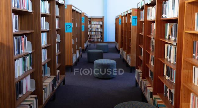 Внутрішня частина бібліотеки з сидіннями і рядами книжкових полиць. — стокове фото