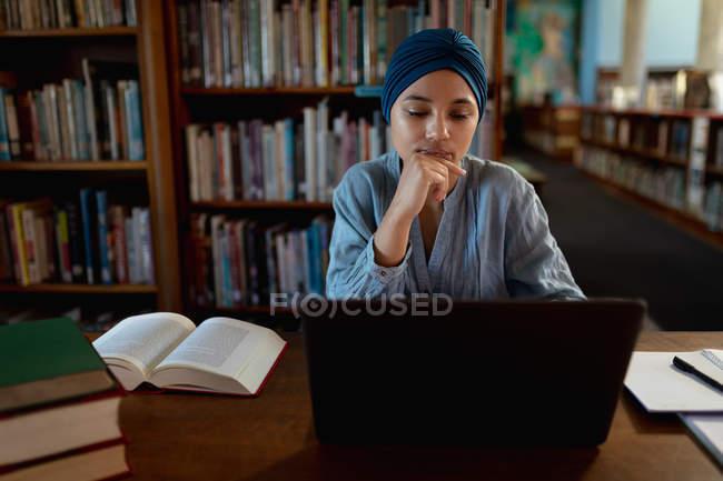 Vue de face gros plan d'une jeune étudiante asiatique portant un turban utilisant un ordinateur portable et étudiant dans une bibliothèque — Photo de stock