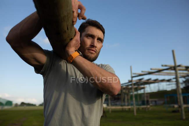 Вид спереди на молодого кавказца, несущего дрова в открытом спортзале во время тренировочного лагеря — стоковое фото