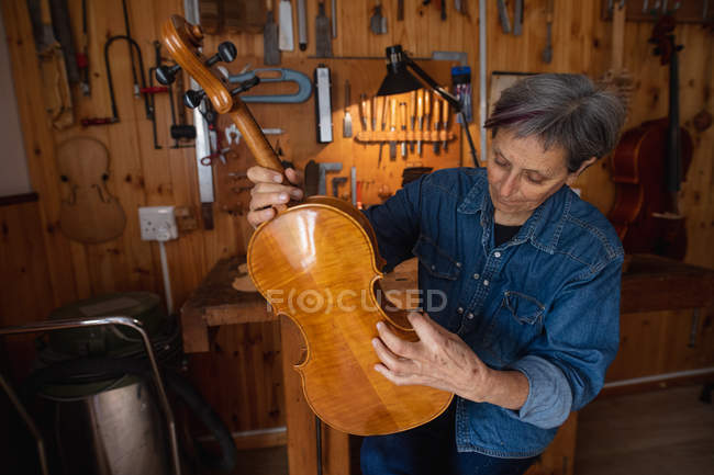 Front view of a senior Caucasian female luthier holding a violin in her workshop, with tools hanging up on the wall in the background — Stock Photo