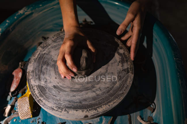 Elevated close up of the hands of female potter shaping clay on a potters wheel in a pottery studio — стокове фото