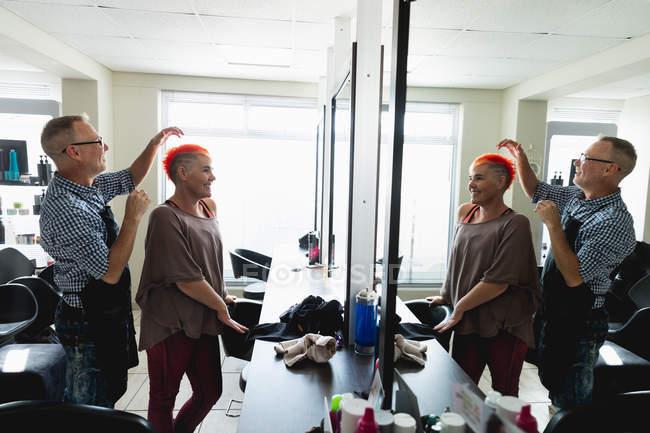 Бічний вид на кавказьку перукарку середнього віку і молоду кавказьку жінку з яскраво-червоним волоссям в салоні для волосся, відбитим у дзеркалі. — стокове фото