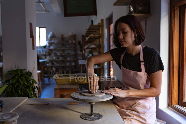 Side view of a young Caucasian female potter sitting at a work table working with clay on a banding wheel in a pottery studio — Stock Photo