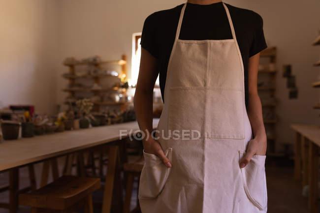 Вид спереди, средняя часть горшечницы, стоящей с руками в карманах фартука в мастерской керамики. — стоковое фото