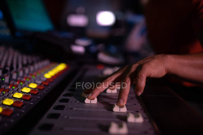 Close up of the hand of male sound engineer pushing up three fader controls on a mixing desk in a recording studio — Stock Photo