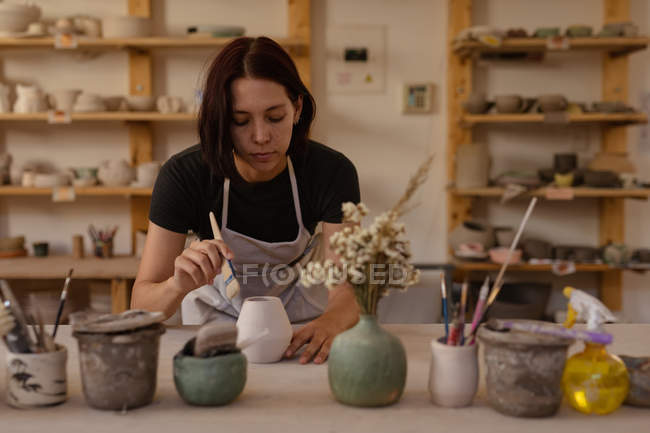Front view close up of a young Caucasian female potter leaning over a work table and glazing a pot in a pottery studio, with pots and tools in the foreground — Stock Photo