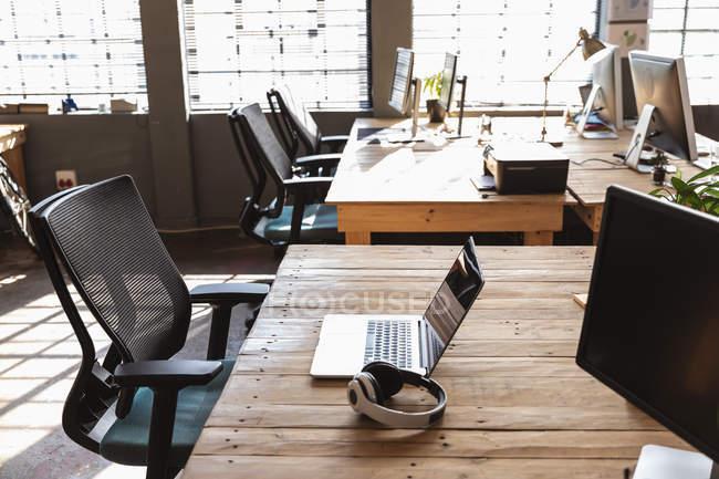 Seitenansicht von Stühlen am Schreibtisch mit Computermonitoren, einem Laptop und einem Kopfhörer darauf in einem kreativen Büroraum, der von Sonnenlicht aus großen Fenstern im Hintergrund beleuchtet wird — Stockfoto