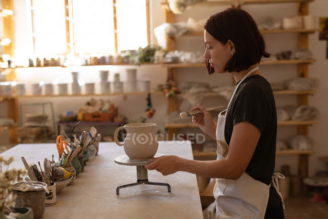 Side view of a young Caucasian female potter at a work table with pots of tools on it, glazing a jug on a banding wheel in a pottery studio — Stock Photo