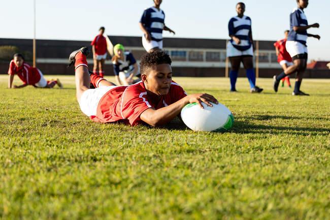 Передній вигляд дорослої змішаної раси Жіночий регбі-гравець лежить на полі і тримає м'яч, щоб забити спробу під час матчу регбі, з товаришами по команді і супротивниками на задньому плані. — стокове фото