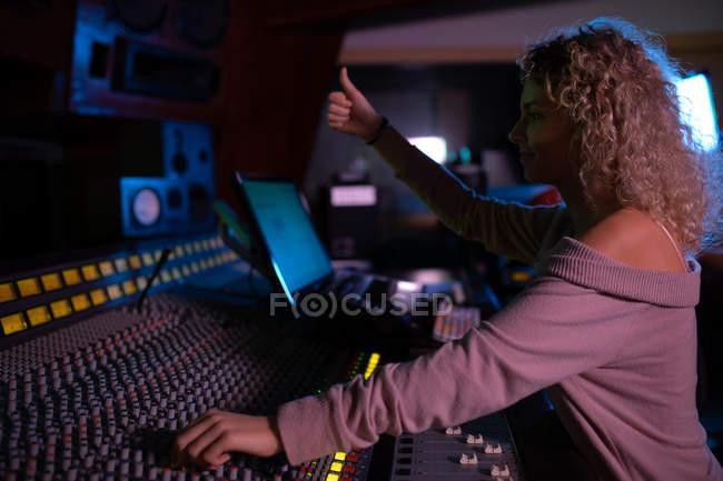 Vista lateral de perto de uma jovem engenheira de som caucasiana trabalhando em uma mesa de mistura em um estúdio de gravação dando um sinal de polegar para cima durante uma sessão de gravação — Fotografia de Stock