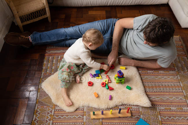 Side view of a young Caucasian father playing with his baby on a floor — Stock Photo