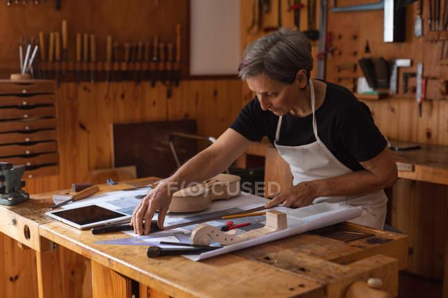 Вид со стороны старшей белой женщины-лютиристки, меряющей на верстаке в мастерской, с планшетным компьютером перед ней и инструментами, висящими на стене на заднем плане — стоковое фото