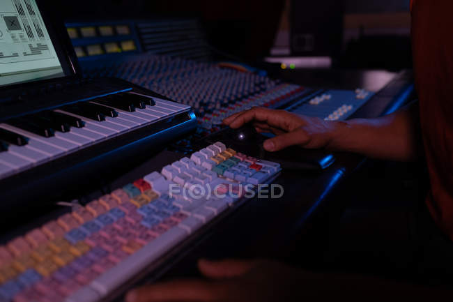 The hand of male sound engineer using a computer mouse at a mixing desk in a recording studio — Stock Photo