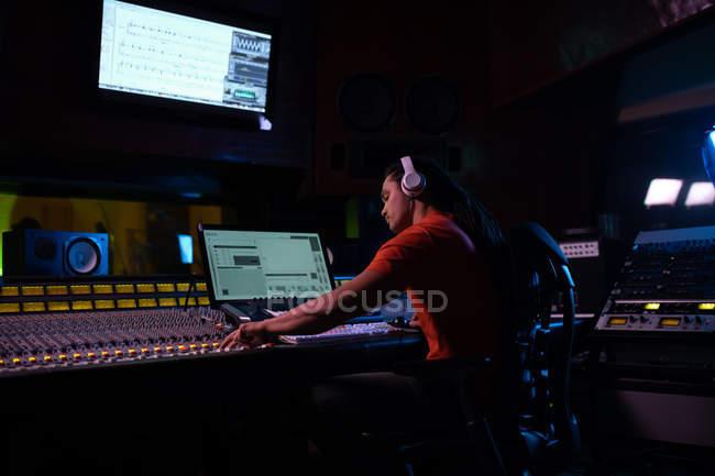 Vista lateral de um jovem engenheiro de som misto sentado e trabalhando em uma mesa de mistura em um estúdio de gravação usando um computador e usando fones de ouvido — Fotografia de Stock