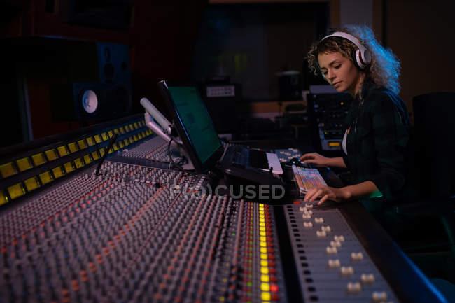 Вид сбоку на молодую кавказскую звукоинженершу, сидящую и работающую за микшерским столом в студии звукозаписи в наушниках — стоковое фото