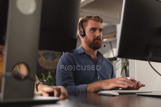 Front view close up of a young Caucasian man sitting at a desk using a computer and wearing a phone headset in a creative office, seen between computer screens, with the hand of a colleague working beside him on the desk — Stock Photo