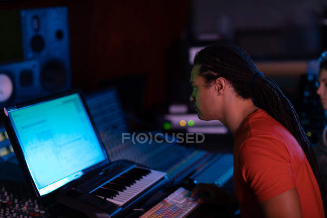 Side view close up of a young Caucasian male sound engineer sitting and working at a mixing desk in a recording studio using a computer — Stock Photo