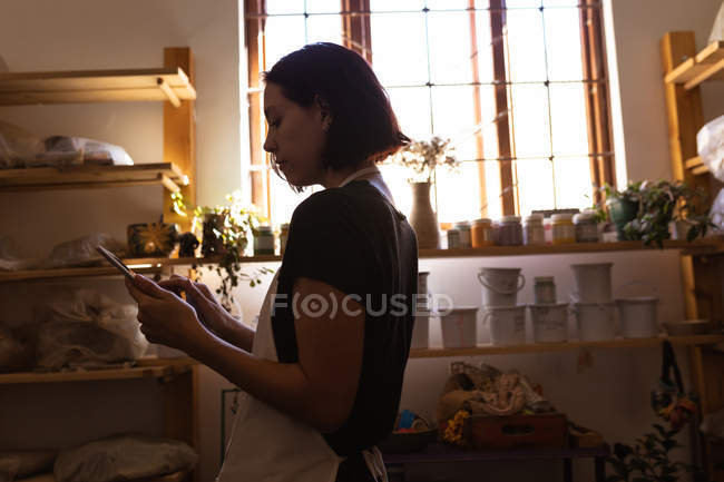 Side view a young Caucasian female potter using a tablet in a pottery studio — Stock Photo