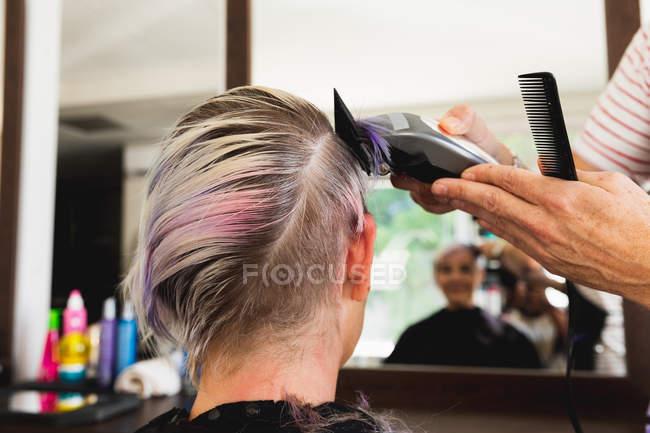 Visão traseira close-up de um cabeleireiro masculino caucasiano de meia idade e uma jovem mulher caucasiana ter seu cabelo aparado em um salão de cabeleireiro, refletido em um espelho — Fotografia de Stock