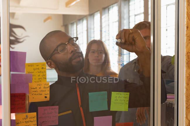 Vista frontale da vicino di un giovane afroamericano con gli occhiali che scrive appunti su una parete di vetro durante una sessione di brainstorming di squadra in un ufficio creativo, visto attraverso una parete di vetro con i colleghi dietro di lui a guardare — Foto stock